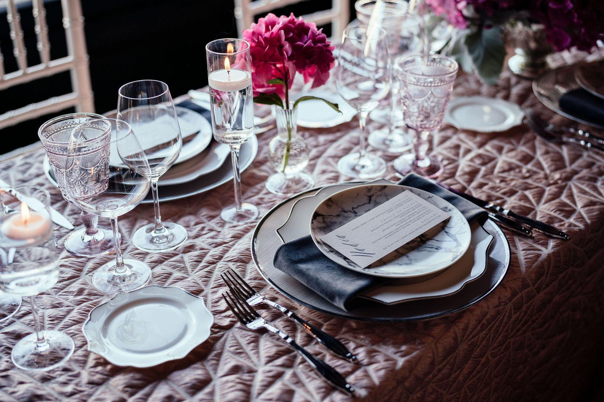 Beautiful table setting with pail pink and textured tablecloth and gray linen napkins
